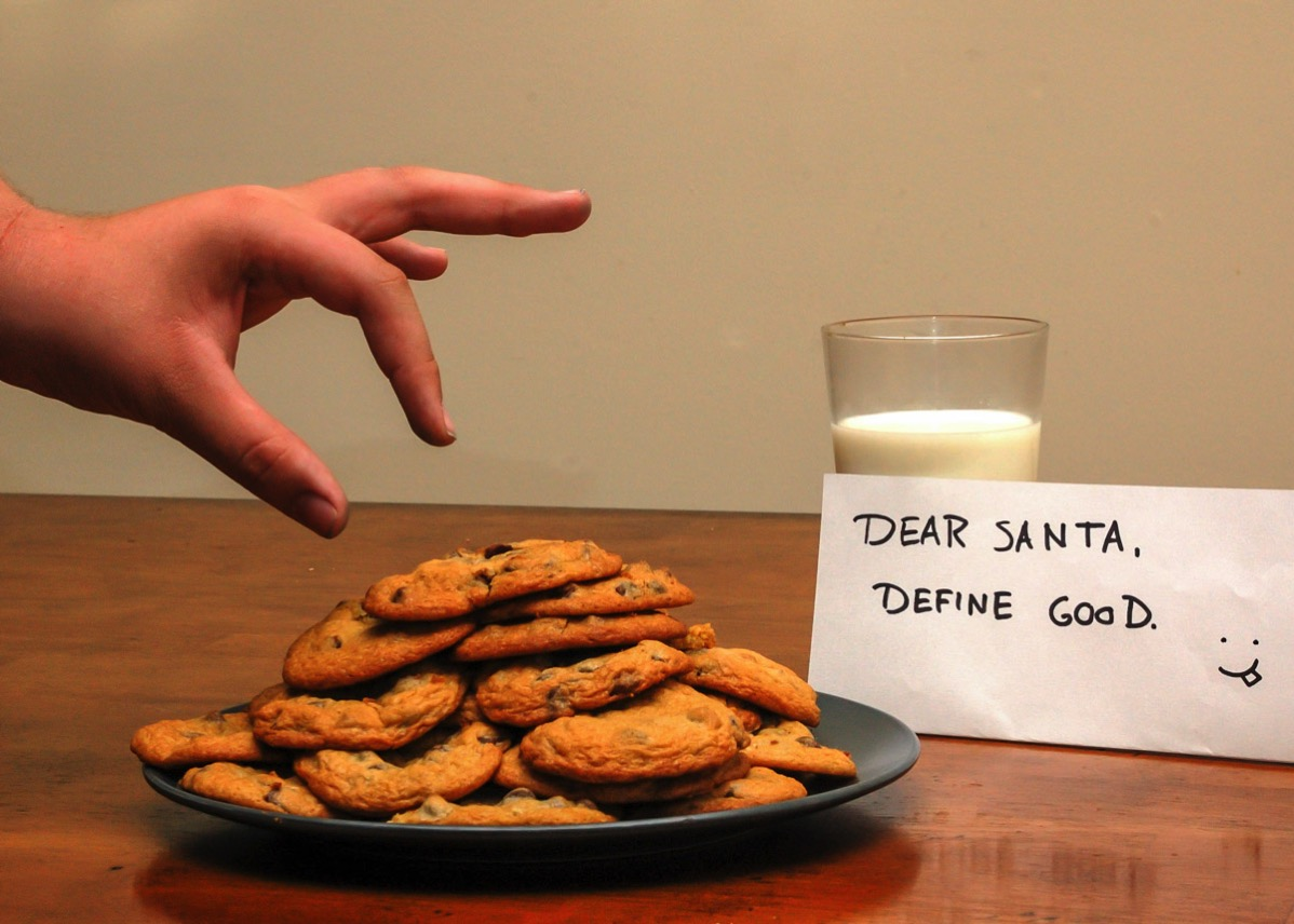 Plate of Christmas cookies and a glass of milk, with an envelope on which is written